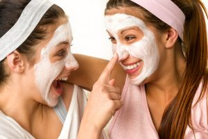 Playful teens wearing a purifying mask for acne-prone skin