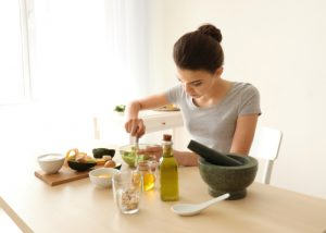 Young woman making skincare mask for Playful teens wearing purifying mask for acne-prone skin with avocado in kitchen
